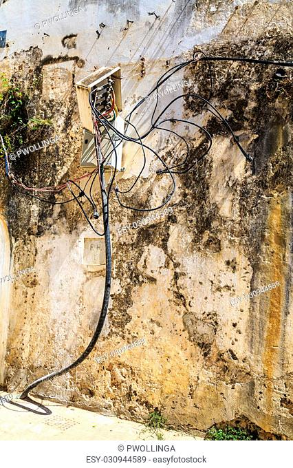 Electricity cables tangled in an connection box on the ouside of a brick wall