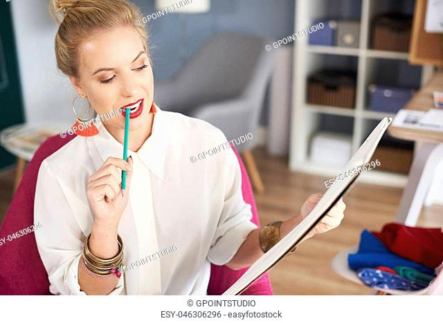 Woman holding pencil in her mouth