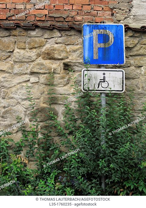 dirty road signs for people with disabilities in a dark corner parking, Lower Saxony, Germany