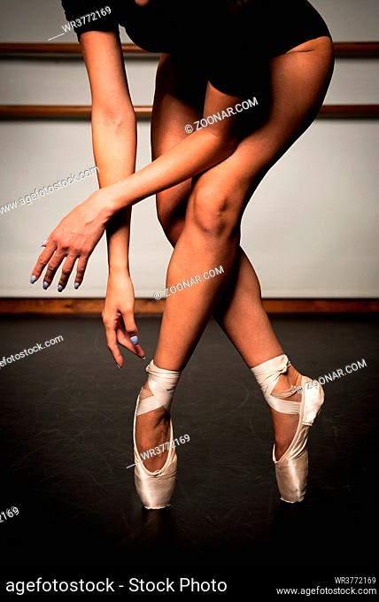 Beautiful legs of young ballerina with pointe shoes dancing on a black floor background. Ballet practice. Beautiful slim graceful feet of ballet dancer