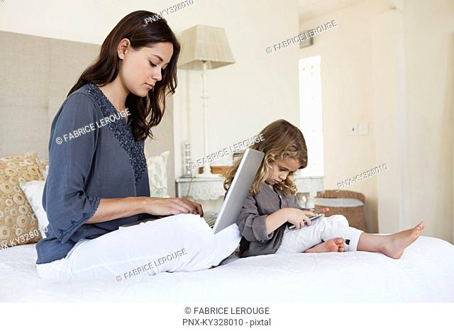 Woman working on a laptop with her daughter playing with a mobile phone beside her