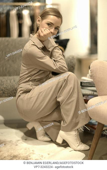 side view of fashionable wealthy blogger woman crouching indoors on carpet in clothing store, aspiration, in Munich, Germany