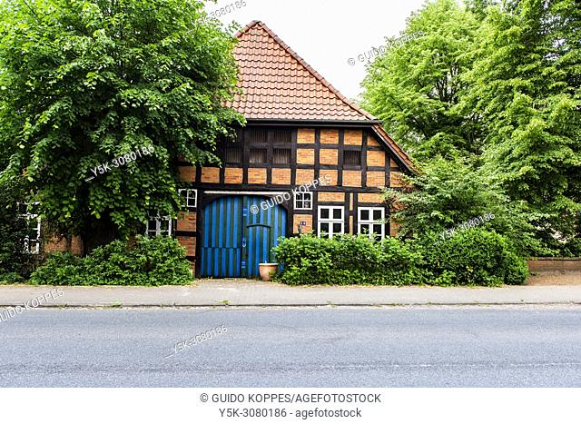 Niedersachsen, Germany. Exterior of a farmhouse stable with a huge barn doors and trees bordering the building. Traditional FachWerk House