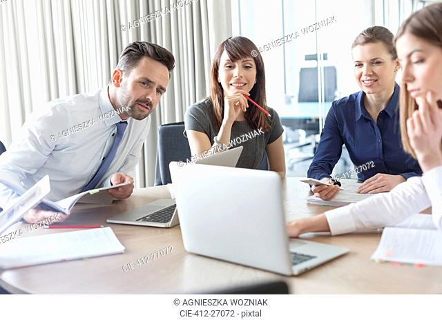 Business people working at laptop in conference room