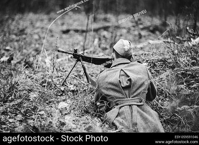 Re-enactor Dressed In Overcoat As World War II Russian Soviet Red Army Soldiers Hidden Aiming With Machine Gun In Forest Ground