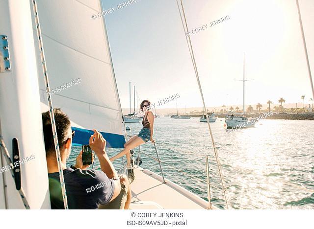 Couple taking photograph on sailboat, San Diego Bay, California, USA