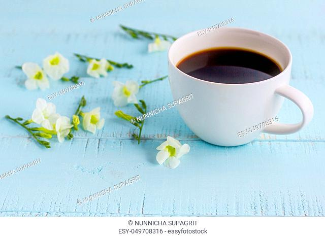 White coffee cup with black coffee and flowers on wooden table