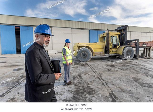 Businessman and female worker on industrial site near bulldozer