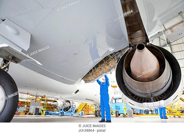 Engineer looking up at flap on wing of passenger jet in hangar