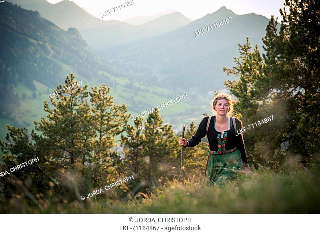 Young woman in traditional costume hiking on the Falkenstein in the Allgaeu, Pfronten, Bavaria, Germany