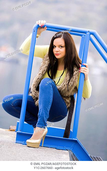 Young woman framed by metal fence
