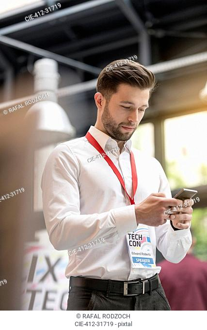 Man texting with cell phone at technology conference