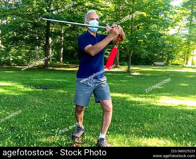 A man wearing a mask practices Tai-chi with a sword in a park, Ontario, Canada. This is a modified form of the traditional Chinese martial art