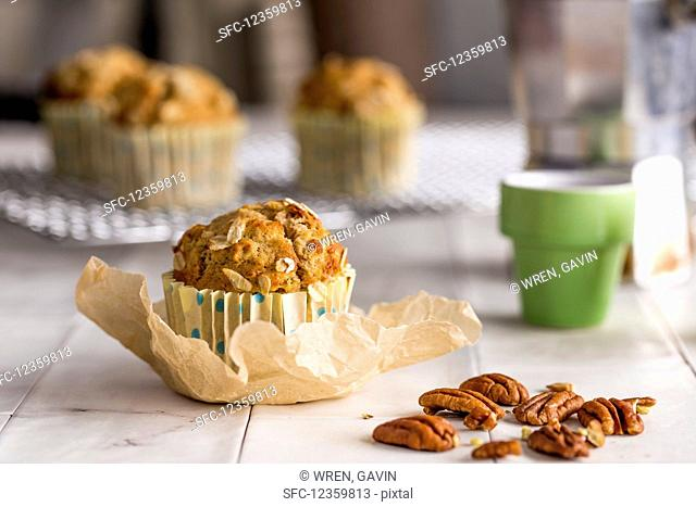Spelt banana maple pecan oat and nut muffin in baking sheet with espresso coffee, moka pot and further muffins sitting on a cooling rack