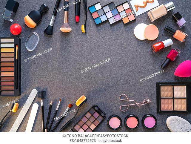 Cosmetics makeup lipstick eye shadows arrangement on glitter dark gray table