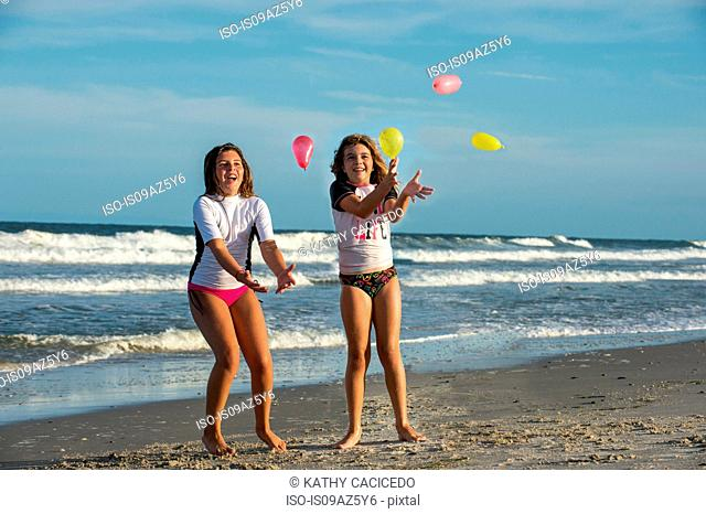Two young sisters playing with small balloons on beach