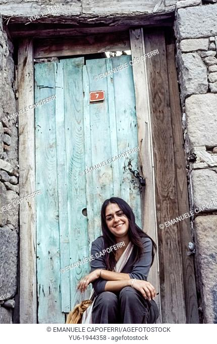 portrait of woman sitting in front of a colored door, Turkey
