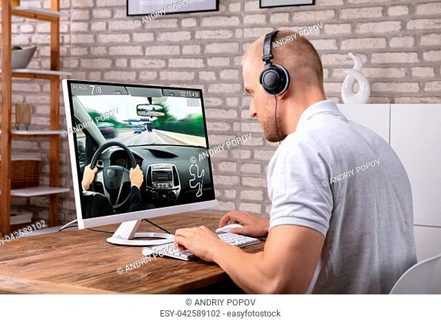 Young Man With Headphone Playing Car Game On Computer Over Desk