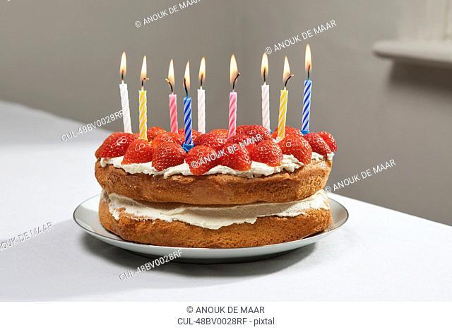 Lit candles on birthday cake