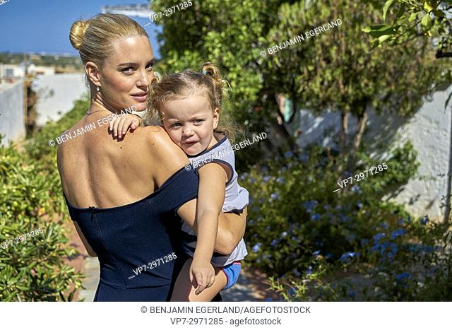 mother carrying daughter on shoulder in garden. Australian ethnicity