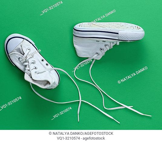 pair of white old textile sneakers with untied laces on a green background, top view