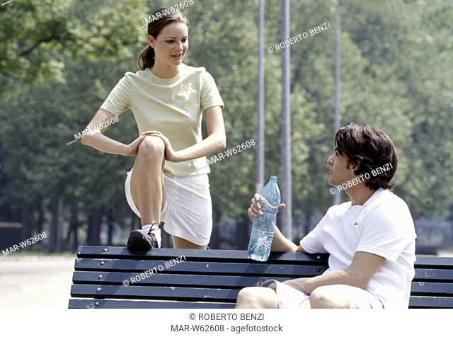 couple stretching, bench