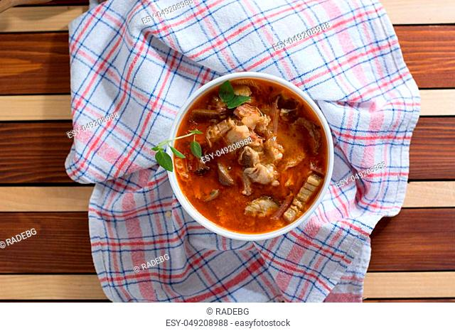 Traditional and very popular serbian dish from beef tripe served on wooden table