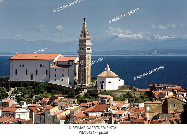 Piran Slovenia with St George's Cathedral belfry and baptistery on the Gulf of Trieste with snow capped Kanin mountains and distant Monfalcone Italy