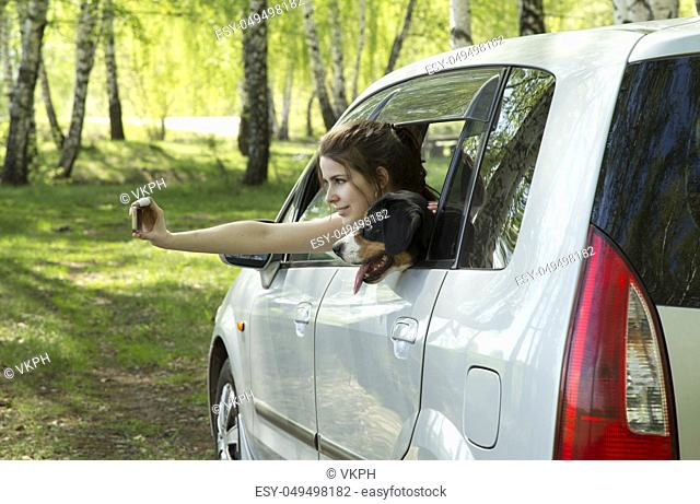 Young woman and dog taking selfie in car in spring forest