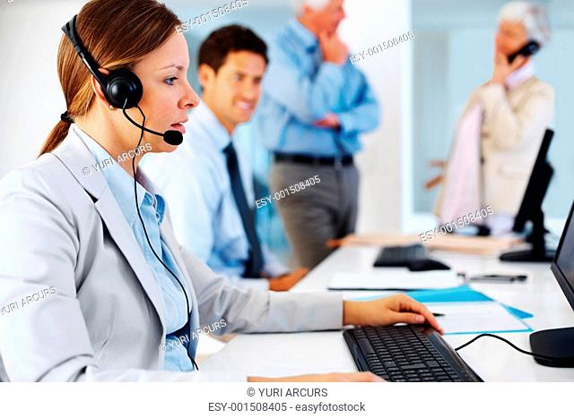 Young female executive using headset and computer with colleagues in background