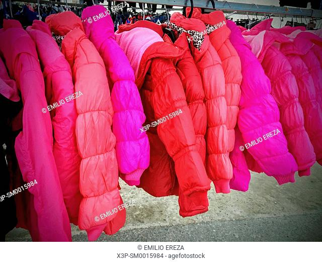 Pink and red coats for sale in a market