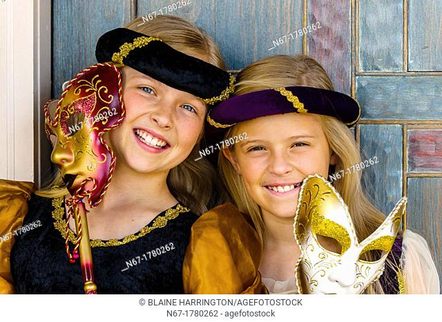 Preteen sisters dressed in medieval costumes and holding Carnival masks, Cedar City, Utah USA  Cedar City is home to the Tony Award-winning Utah Shakespeare...