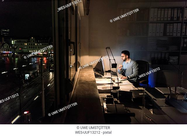 Businessman working on computer in office at night