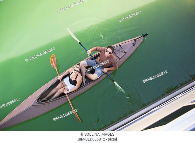 Caucasian couple rowing canoe
