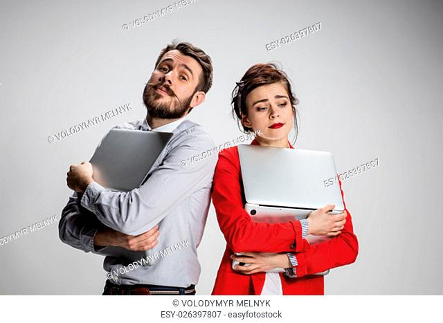 The young businessman and businesswoman with laptops posing on gray background. The concept of relationship of colleagues and of love in the work