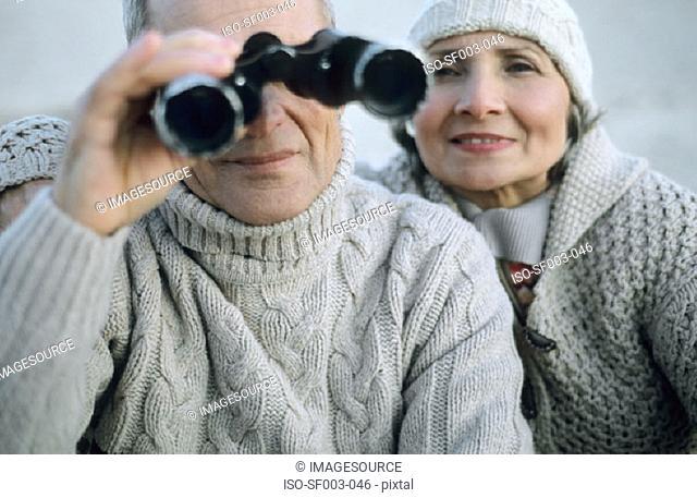 Senior couple using binoculars