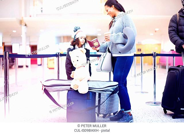 Girl and mother looking at passport in airport departure lounge