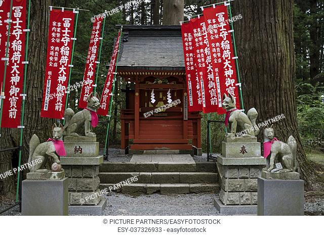 Votive Kitsunes, fox figurines, animal guardians in front of an Inari Shrine with red shrine banners