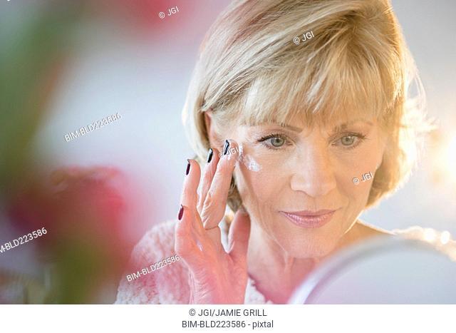 Older Caucasian woman applying moisturizer to face