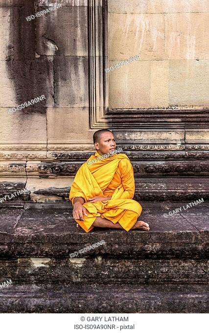 Young Buddhist monk sitting at temple in Angkor Wat, Siem Reap, Cambodia