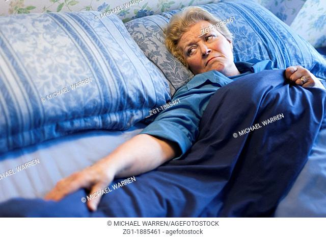 Mature woman lying in bed and looking at the empty space next to her
