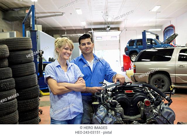 Portrait confident mechanics at engine auto repair shop