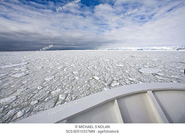 The Lindblad Expeditions ship National Geographic Explorer pushes through ice in Grandidier Channel, a navigable channel between the west coast of Graham Land...