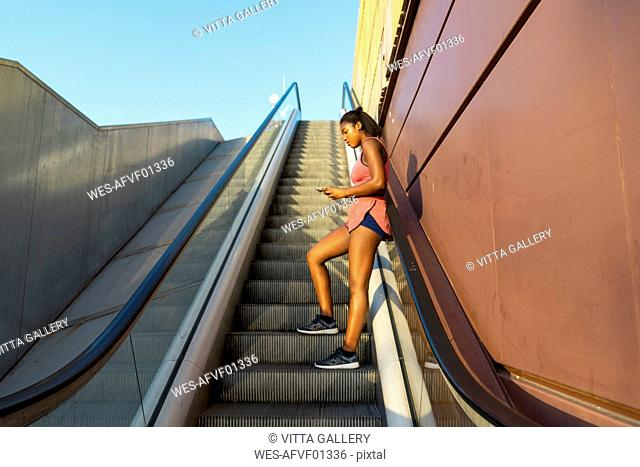 Young sportive woman on escalator using smartphone