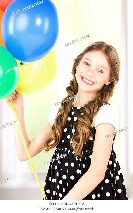 happy girl with colorful balloons at home