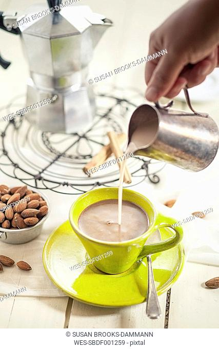 Woman's hand pouring almond milk into cup of coffee