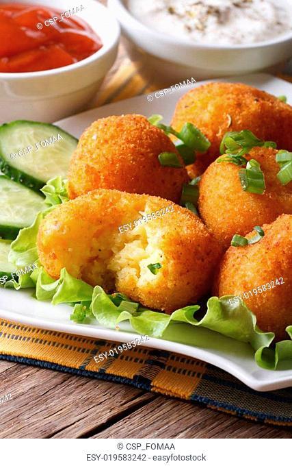 Potato balls deep fried on a plate vertical