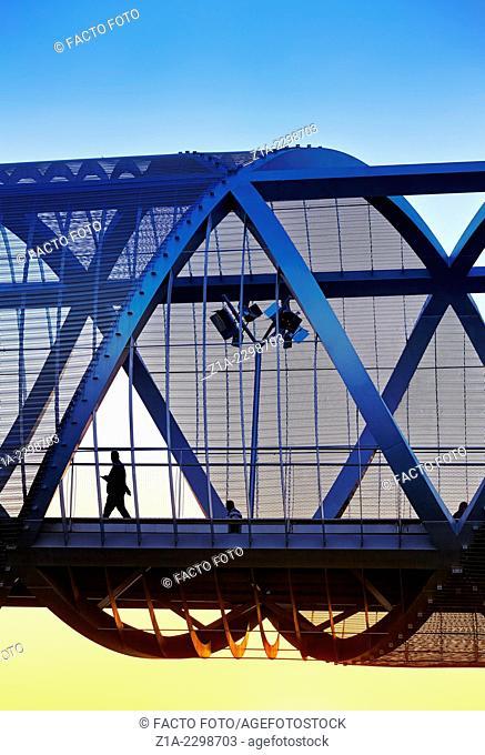 Silhouette passing by the Arganzuela bridge, designed by architect Dominique Perrault. Madrid Rio Park. Madrid. Spain