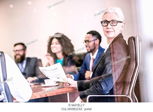 Businesswoman looking over her shoulder in board team meeting