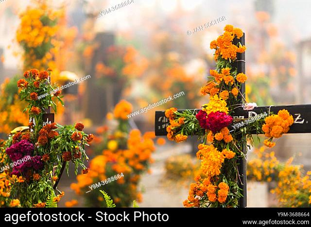 Grave crosses, decorated with marigold flowers, are seen at a cemetery during the Day of the Dead celebrations in Ayutla, Mexico, 2 November 2019